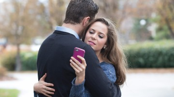 An embracing couple is distracted by cell phones.